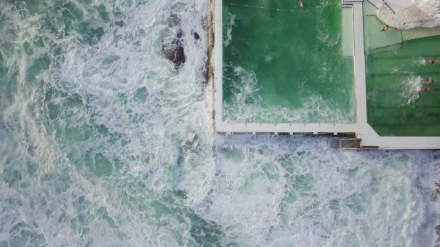 vídeos de stock, filmes e b-roll de aerial ascent: large storm waves break into swimming pool, bondi beach, australia - sydney australia