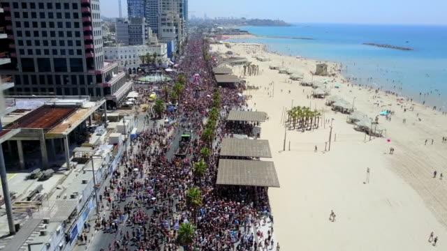 vidéos et rushes de aerial ascent: pride parade on scenic promenade along beautiful seashore, tel aviv, israel - touriste