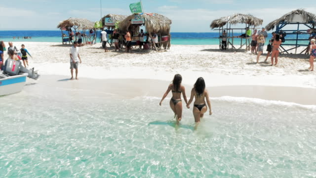 vídeos de stock, filmes e b-roll de aerial ascent: two young women on small island surrounded by bright blue water - rodeando
