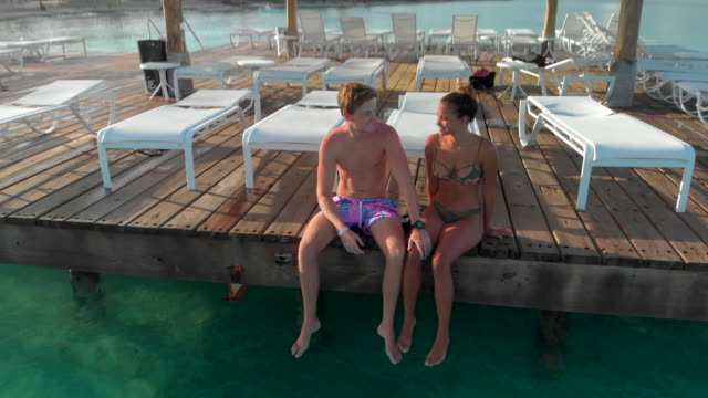 aerial ascent: young couple on dock on bright blue ocean - zurücklehnen stock-videos und b-roll-filmmaterial