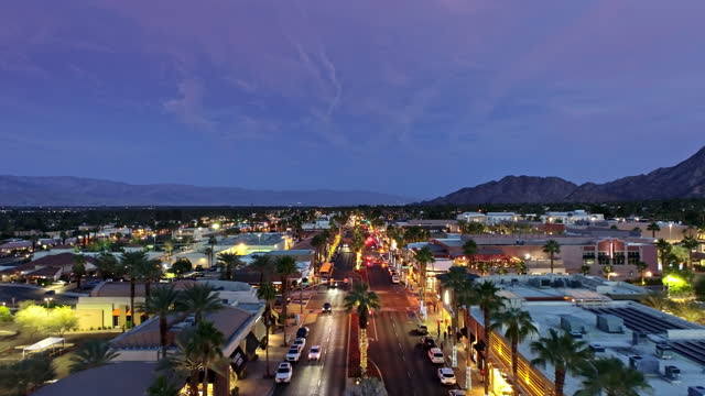 ws aerial at dusk over downtown palm desert business district surrounded by mountains of the coachella valley - straßenschild stock-videos und b-roll-filmmaterial