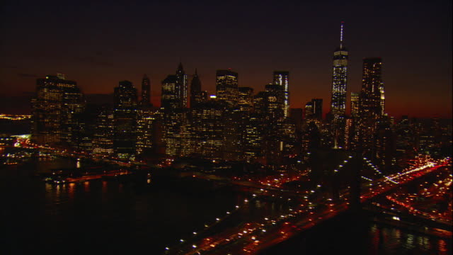 aerial -at night, a low pass over the manhattan and brooklyn bridges with a tilt up to reveal the freedom tower, then wrapping around lower manhattan to the staten island ferry terminal. - world trade centre manhattan stock videos and b-roll footage