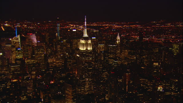 Aerial -At night, flying north over Manhattan with a slow ZI to include the Empire State building passing in front of the Chrysler building.