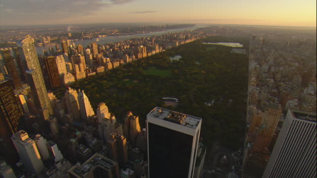 aerial -at sunrise, flying from mid-town manhattan skyline toward central park. - central park manhattan stock videos and b-roll footage