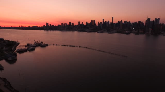 aerial at sunrise over hudson river looking at silhouette of midtown manhattan, nyc  - orange new jersey stock videos & royalty-free footage