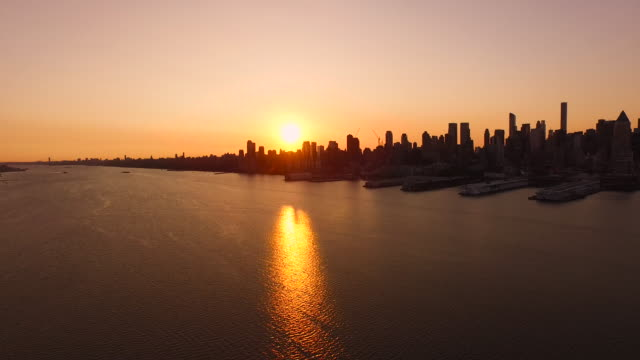 aerial at sunrise over hudson river looking at silhouette of manhattan sun shinning behind buildings, nyc  - orange new jersey stock videos & royalty-free footage