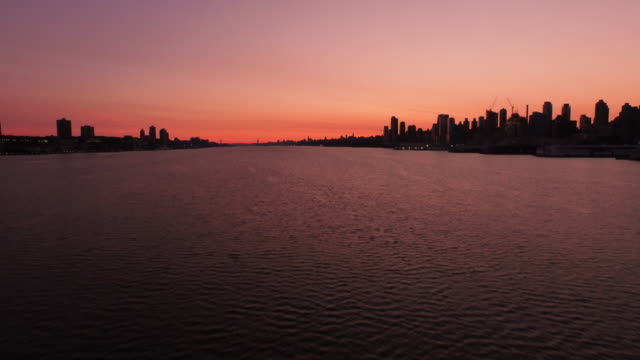 aerial at sunrise over hudson river looking north at silhouette of manhattan and new jersey, nyc  - orange new jersey stock videos & royalty-free footage