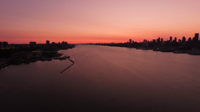 aerial at sunrise over hudson river rising up looking at silhouette of manhattan and new jersey, nyc  - orange new jersey stock videos & royalty-free footage