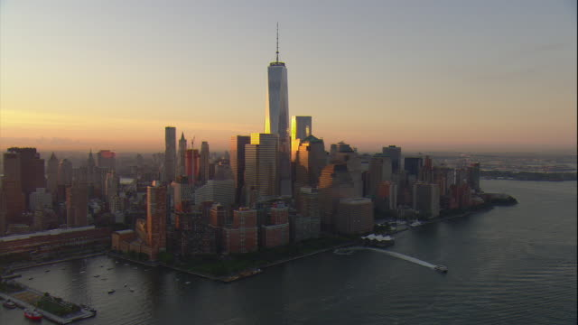 Aerial -At sunrise over the Hudson River, sun reflecting on the lower Manhattan skyline including the Freedom Tower.