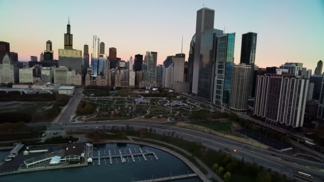 aerial at sunrise panning northwest to southwest over chicago skyline and harbor - shedd aquarium stock videos and b-roll footage