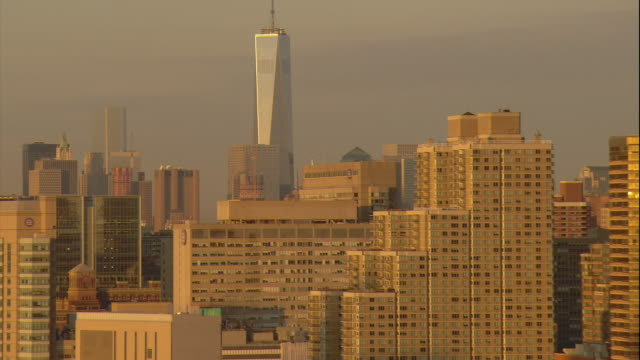 Aerial -At sunrise, traffic on FDR drive in Manhattan with a tilt up to reveal the Freedom Tower.