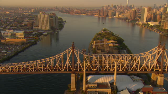 aerial -at sunrise, traffic on the queensboro bridge with a zo and pan to reveal part of roosevelt island, the east river, and manhattan skyline, with the freedom tower visible. - queensboro bridge stock videos & royalty-free footage