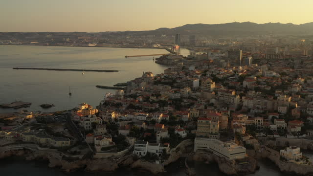 aerial at sunrise while the camera looks over the populated coastline and moves slowly backward and left toward the water moving over the port city of marseille, france, the sun just out of frame on the right. - french culture stock videos & royalty-free footage