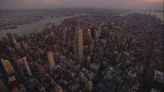 aerial -at sunset, from over times square a tilt up to reveal the empire state building and lower manhattan and the freedom tower in the distance. - one world trade center stock-videos und b-roll-filmmaterial