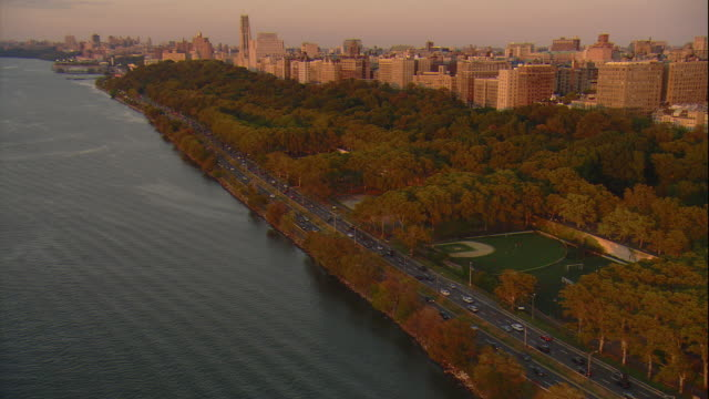 Aerial -At sunset, oblique shot looking down at traffic on the Henry Hudson Parkway with residential buildings of Manhattan behind.