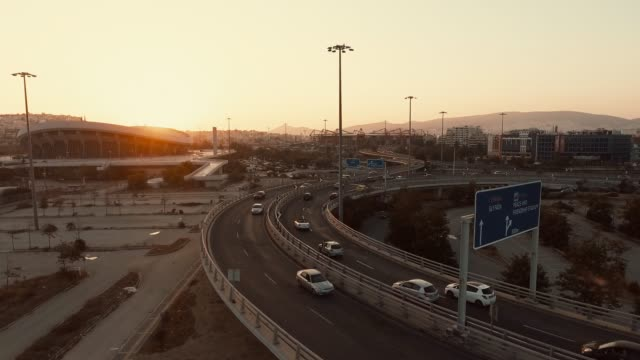 Aerial - Athens - Piraeus - Pireas, Greece, flying above a traffic hub, bridges, tram, cable car and cars at sunset
