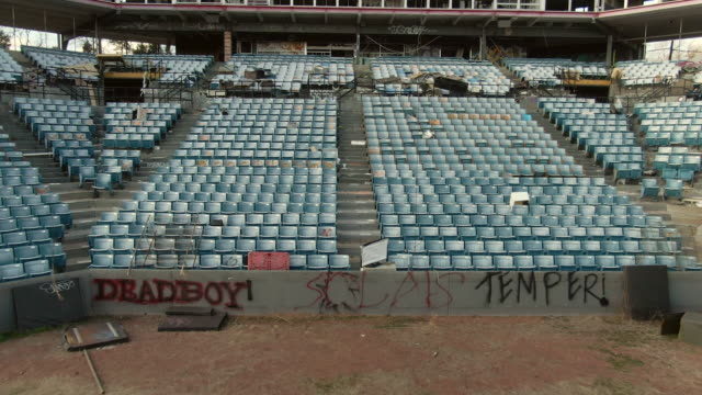 aerial back: bleachers and home plate box falling into disrepair in an abandoned minor league stadium - remote location stock videos & royalty-free footage