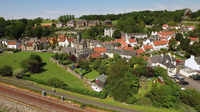 aerial back: brightly tiled cottages clustered together in a quaint village on verdant hill in the sunshine - culross, scotland - cottage stock videos & royalty-free footage