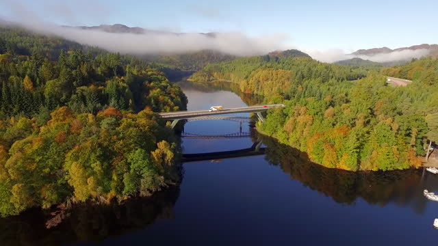 aerial back: traffic speeds across bridge over still river surrounded by autumnal trees and distant hills in sunshine - perth, scotland - evergreen stock videos & royalty-free footage