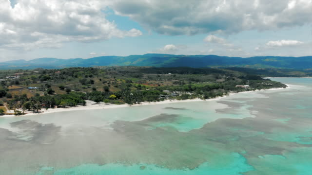 aerial backward: beautiful tropical beach with mountains in the distance - hispaniola stock videos & royalty-free footage