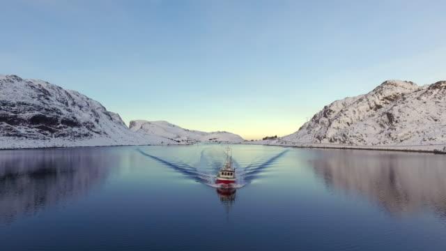 aerial backward: boat cruising on the cold waters of lofoten norway - lofoten, norway - liscio video stock e b–roll