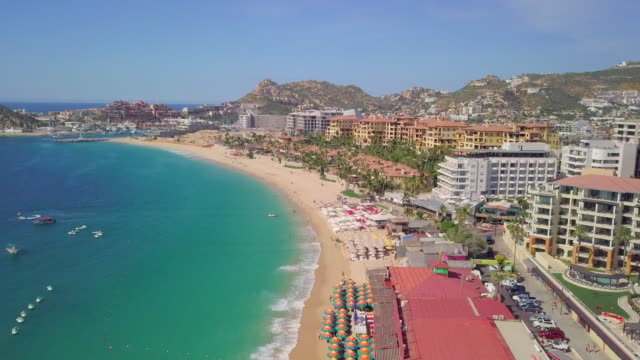 aerial backward: cabo san lucas beachfront - cabo san lucas stock videos and b-roll footage