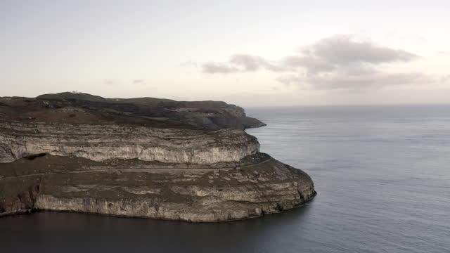 aerial backward: car travelling on the side road of island - llandudno, united kingdom - narrow stock videos & royalty-free footage