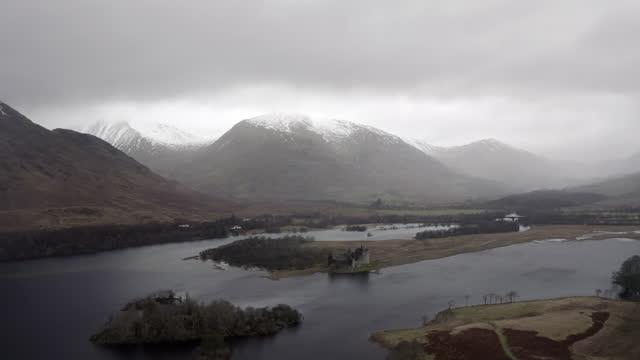 aerial backward: castle ruins near a mountain surrounded by water - argyll and bute,, scotland - skottland bildbanksvideor och videomaterial från bakom kulisserna