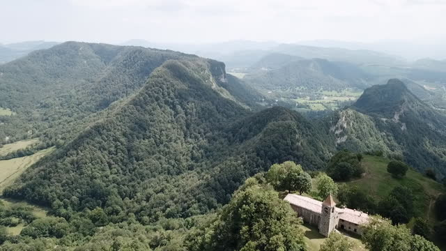 aerial backward: church building on mountain during sunny day - rupit, spain - spanien stock-videos und b-roll-filmmaterial