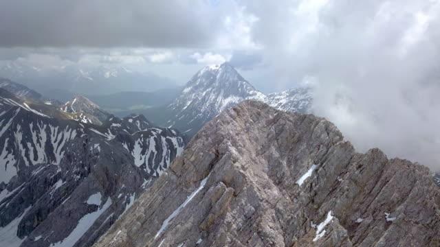 vídeos de stock, filmes e b-roll de aerial backward descending: magnificent mountains of zugspitze munich of germany - munich, germany - montanha zugspitze