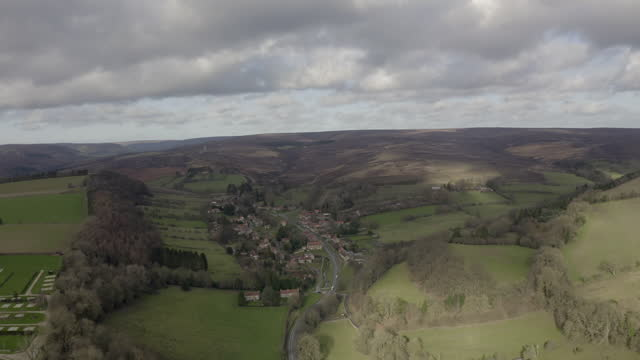 aerial backward: homes in the remote area surrounded by fields - north yorkshire, england - village stock videos & royalty-free footage