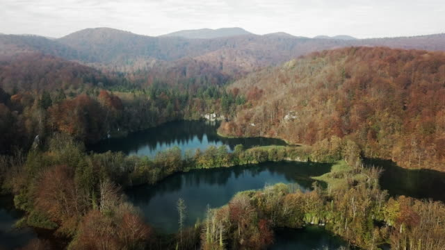 aerial backward: lake reflecting the sky and mountains surrounding it - surrounding stock videos & royalty-free footage