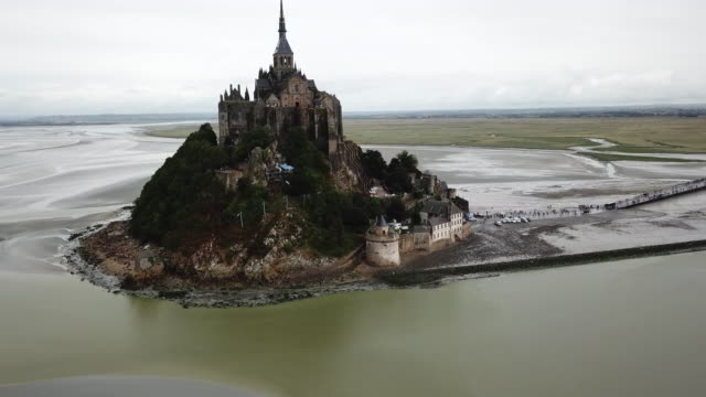 aerial backward: majestic old castle of mont saint michael isolated by water - castle stock videos & royalty-free footage