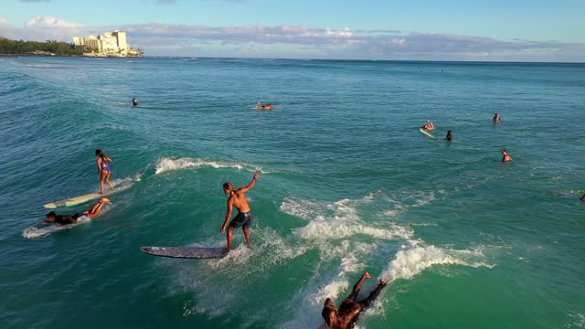 aerial backward panning shot of surfers on vacation surfboarding in sea, drone flying over - oahu, hawaii - oahu stock videos & royalty-free footage