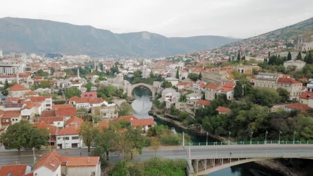 aerial backward: passing under the bridge of stari most with view of city - bosnien und herzegowina stock-videos und b-roll-filmmaterial