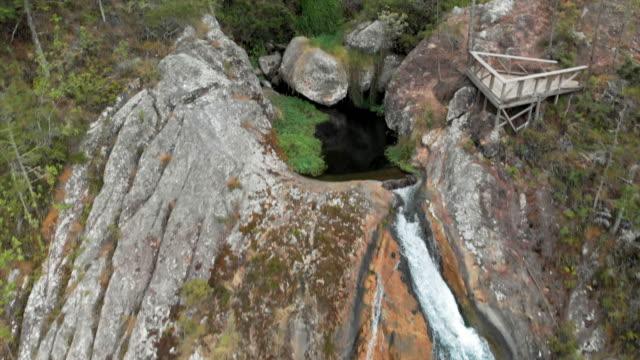 vídeos y material grabado en eventos de stock de aerial backward: scenic waterfall with viewing platform among lush green forest - hispaniola