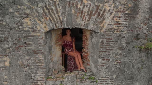 aerial backward: sexy woman posing in castle window in haiti - brick stock videos & royalty-free footage