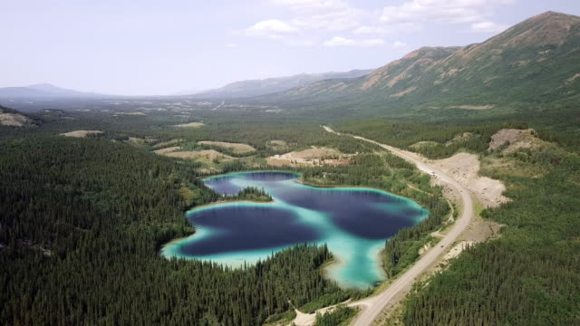 aerial backward slow: small lake in vast area - clear sky stock videos & royalty-free footage