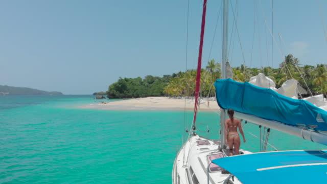 aerial backward: small yacht and island in cocuyo dominican republic - 停泊する点の映像素材/bロール