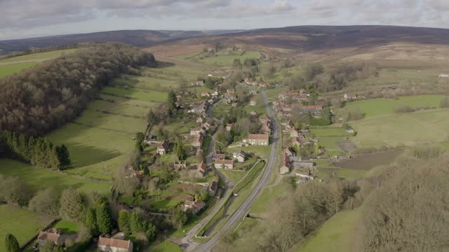 aerial backward: village surrounded by vast fields with clouds - north yorkshire, england - yorkshire england stock videos & royalty-free footage