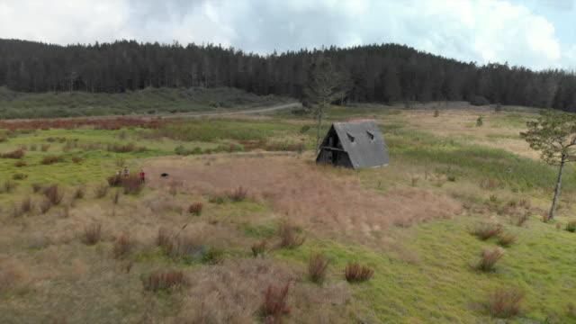 vidéos et rushes de aerial backward: young men in front of scenic ruinous hut next to other ruins - autre thème