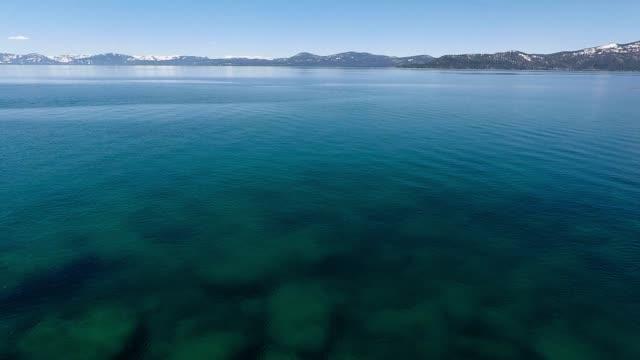 Aerial Backward: Young Woman Stand up Paddleboarding on Beautiful Lake Among Scenic Mountains