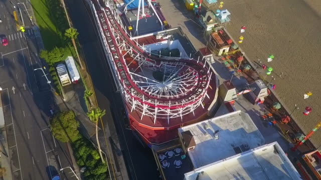 aerial backwards: top of a roller coaster at a boardwalk - cabina del guardaspiaggia video stock e b–roll