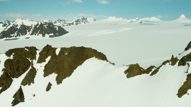 vídeos de stock, filmes e b-roll de aerial barren landscape and snow capped mountains alaska - eco tourism