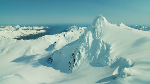 aerial barren landscape and snow capped mountains alaska - gebirge stock-videos und b-roll-filmmaterial