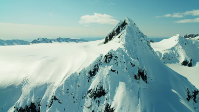 aerial barren landscape and snow capped mountains alaska - 山点の映像素材/bロール