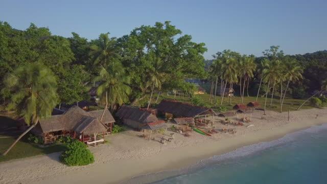 vídeos de stock, filmes e b-roll de aerial: beach huts on the beach of an island in espiritu santo, vanuatu - ilhas do pacífico