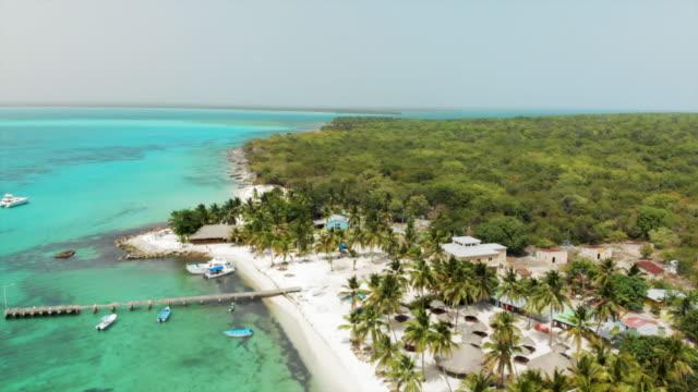 vídeos y material grabado en eventos de stock de aerial: beautiful beach by the ocean with boats by dock - hispaniola