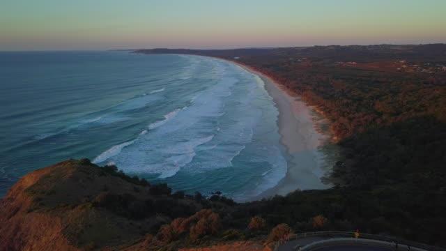aerial: beautiful beach in byron bay at dusk, byron bay, australia - new south wales stock videos & royalty-free footage