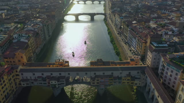 aerial: beautiful cityscape with famous ponte vecchio bridge over river arno at dusk - florence, italy - florenz italien stock-videos und b-roll-filmmaterial
